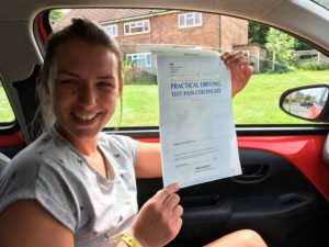 Jess sitting in a car with her pass certificate