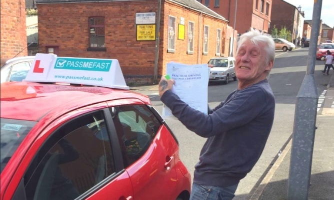 An older driver showing off his practical test certificate
