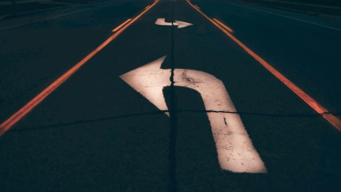 Dark road with arrows pointing in opposite directions.