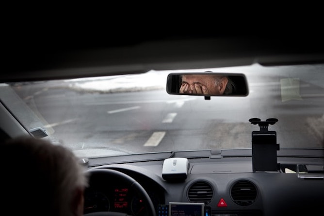 A tired driver shown in the rear view mirror rubbing his eyes