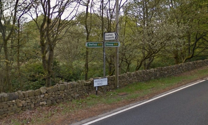 Signpost indicating directions to Sheffield and Glossop on the A57