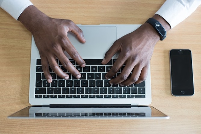 An aerial view of a man's hands typing on a laptop