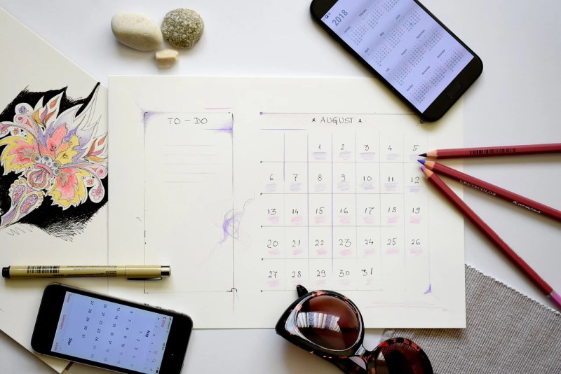 Calendar showing the month of August, surrounded by pencils, a pen, and two smartphones both displaying calendar apps