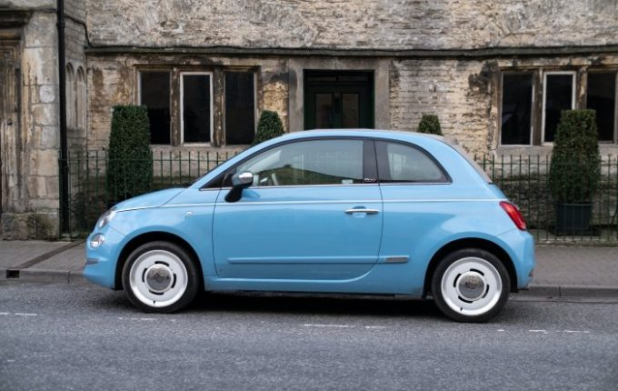 Baby blue Fiat 500 parked on road