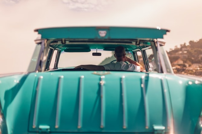 Looking through a turquoise car from its rear bumper