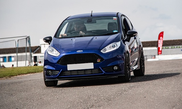The best car to learn to drive in: a blue Ford Fiesta on a race track