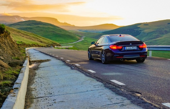 Black BMW driving towards sunrise on empty winding road
