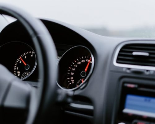 A black car dashboard with a speedometer
