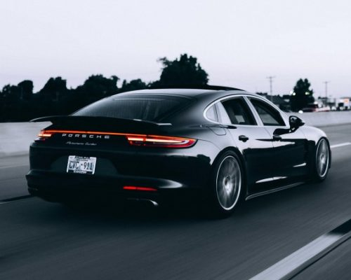 Black Porsche driving down empty road