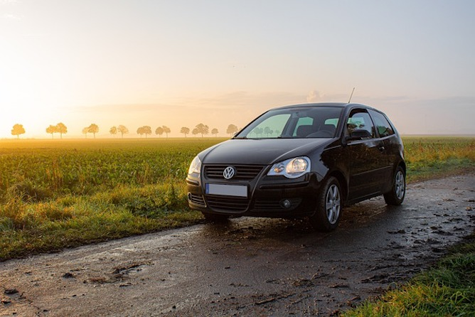 A black VW polo parked on a muddy track with a sunset in the background