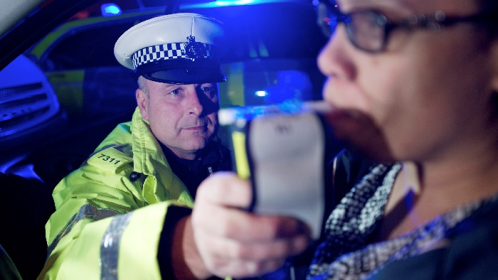 Policeman performing a breathalyzer test
