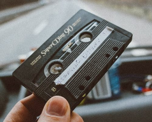 Close up of cassette tape being held in car