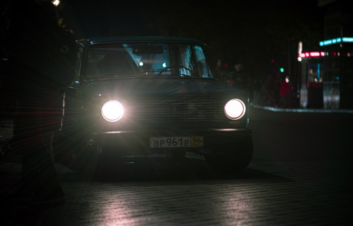 Car driving at night with its full beam headlights lit