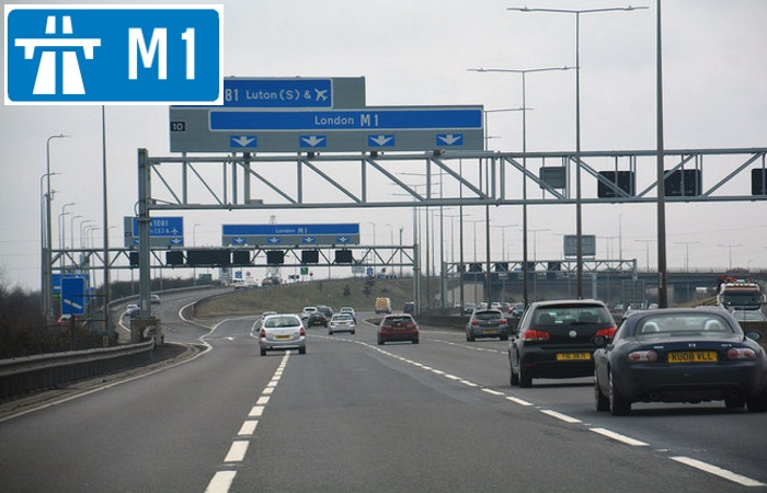 Cars driving on the M1 motorway with sign in corner