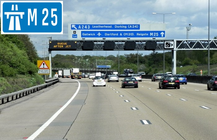 Cars driving on the M25 motorway with sign in corner