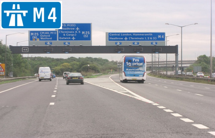 Cars driving on the M4 motorway with sign in the corner