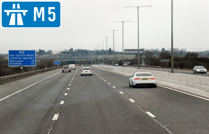 Cars driving on the M5 motorway with sign in corner