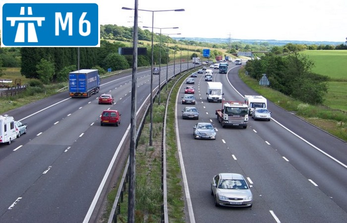 Cars driving on M6 motorway with sign in the corner