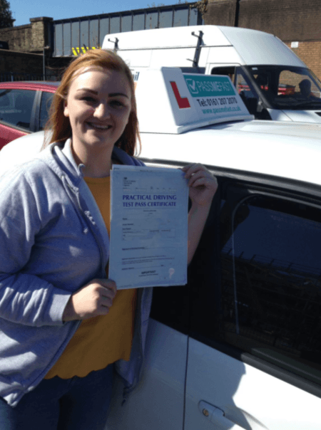 Charlie with her pass certificate standing beside her learner car