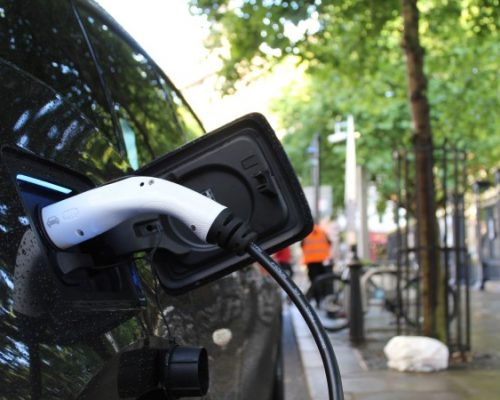 Close up of black electric car charging outside