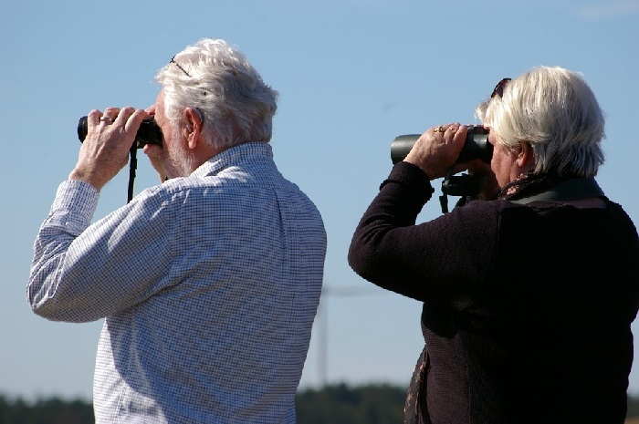 Old man and woman looking through binoculars