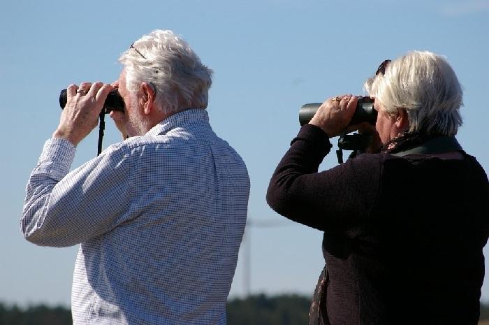 Old man and woman looking through binoculars