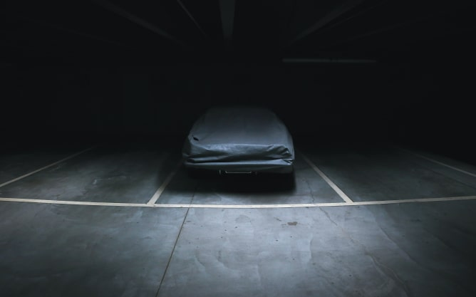 A photograph of a covered car in an otherwise empty garage