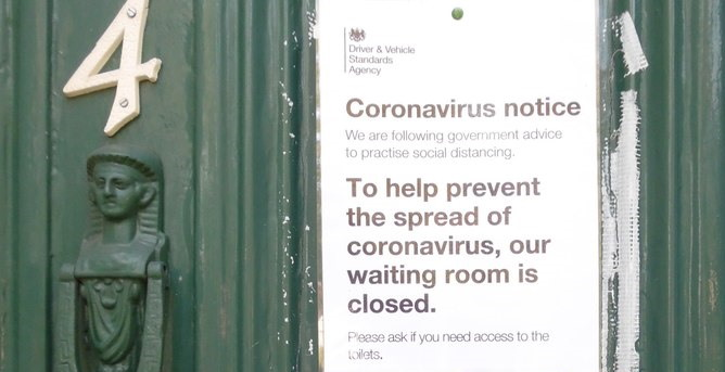 Coronavirus notice on the door of a driving test centre informing candidates that the waiting room is closed