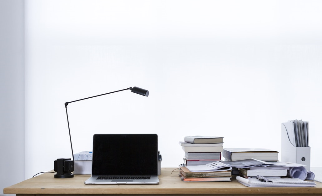 Desk with laptop, lamp, books and papers