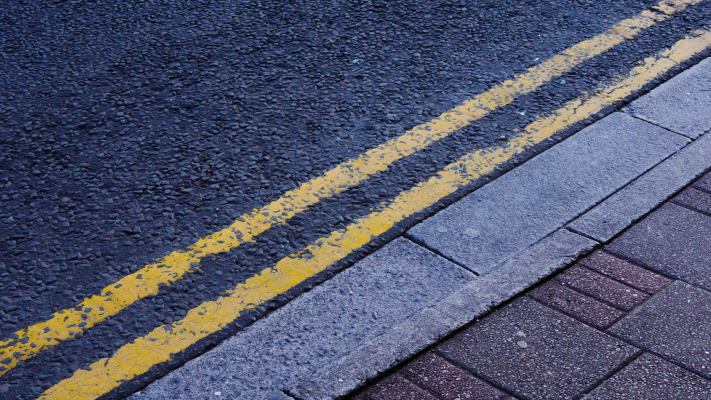Double yellow lines on road next to pavement