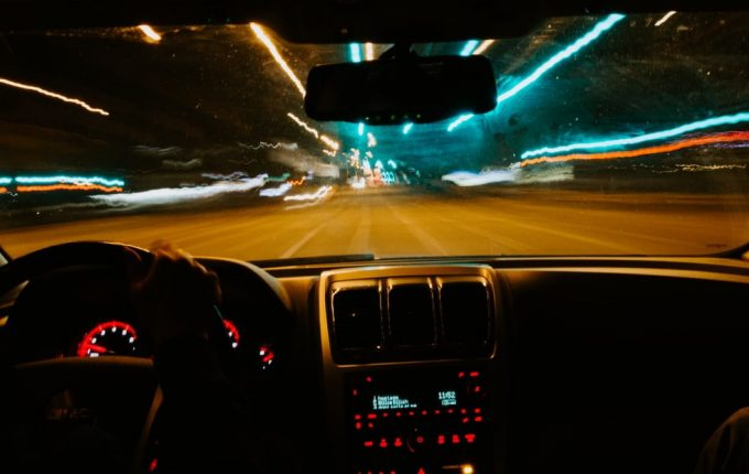 View from car windscreen showing blurred lights on road