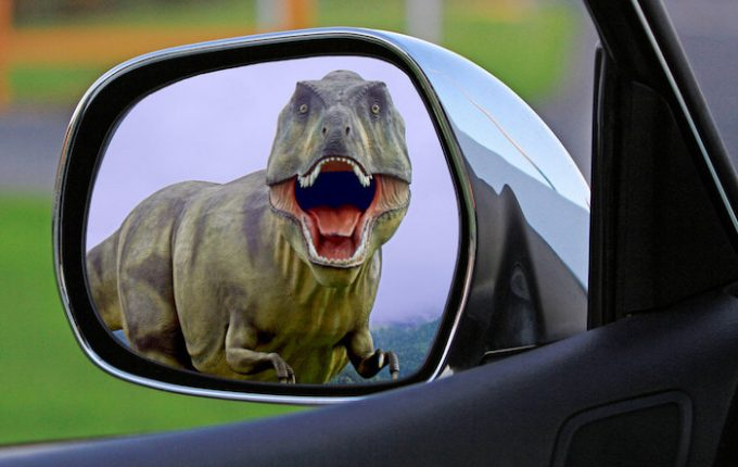 Side mirror showing dinosaur screaming at car