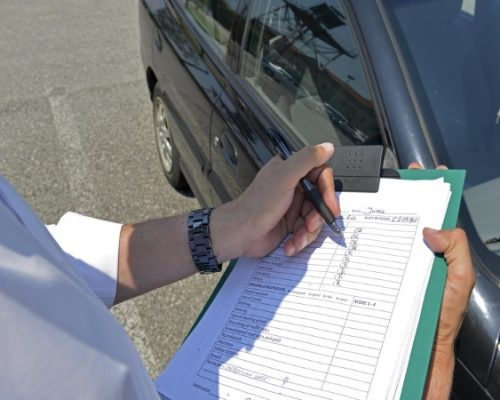 driving examiner marking a practical test sheet