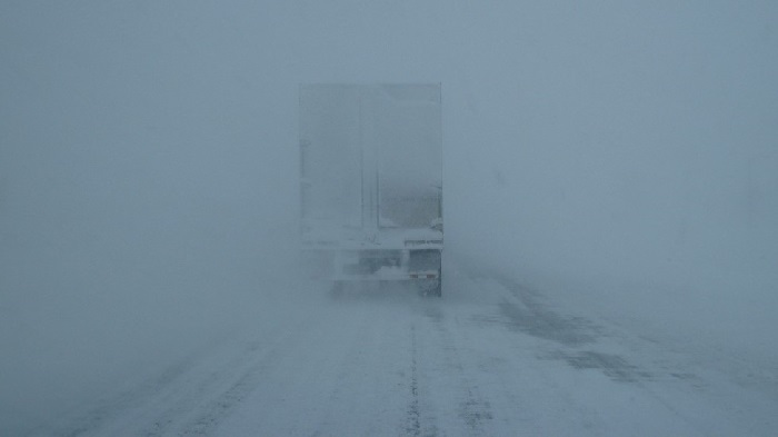 View of the back of a lorry driving during a blizzard