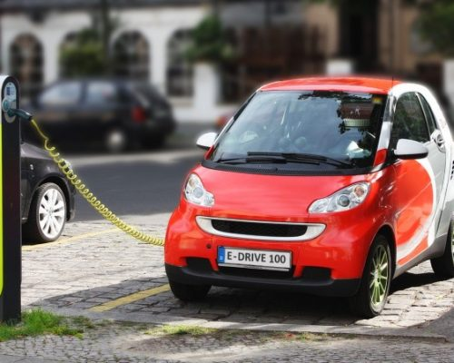An electric car charging at a public charging point