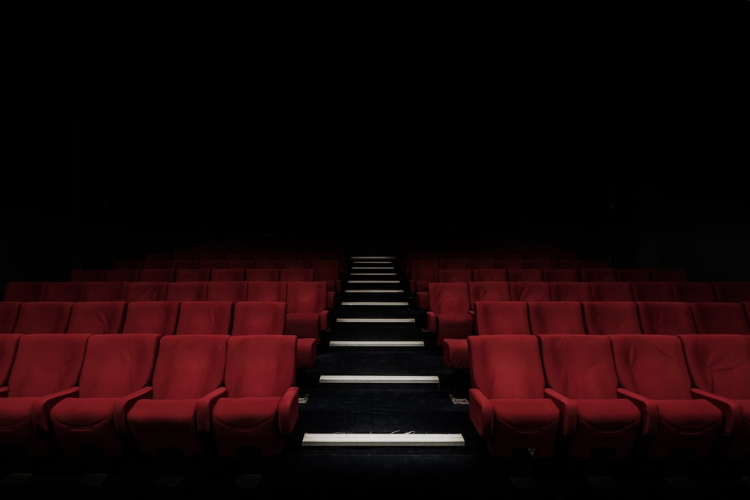 Empty cinema with rows of red seats