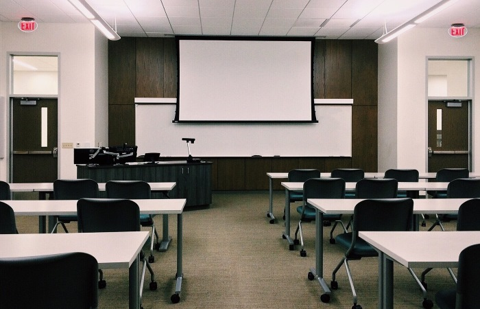 An empty classroom filled with tables chairs and a projector