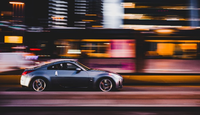 Grey car driving fast against blurred background