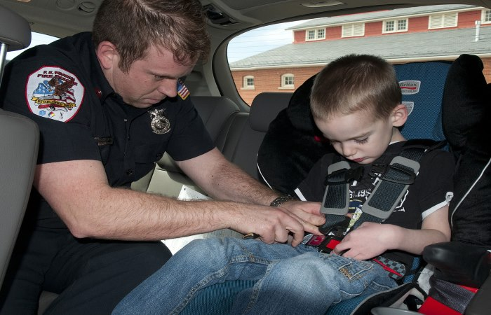 A man fastening a child's seatbelt as another child looks on