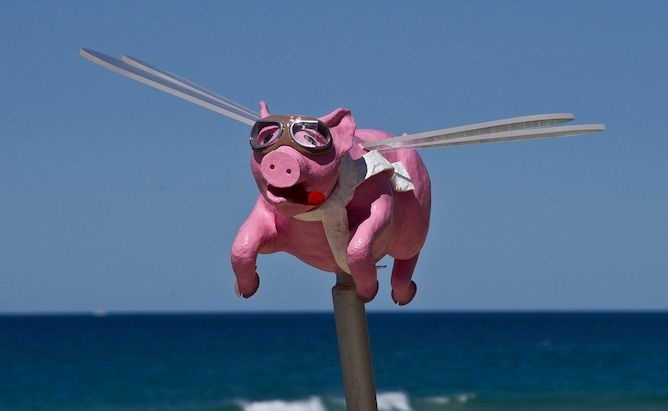 A sculpture of a flying pig with driving goggles on