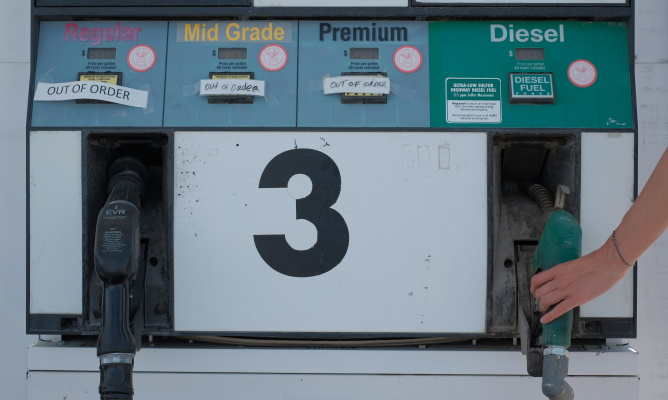"""A fuel pump with the number """"3"""", with separate pumps for """"Regular"""", """"Mid Grade"""", """"Premium"""" and """"Diesel"""" fuels, the first three of which are out of order, and a hand reaching for diesel fuel"""