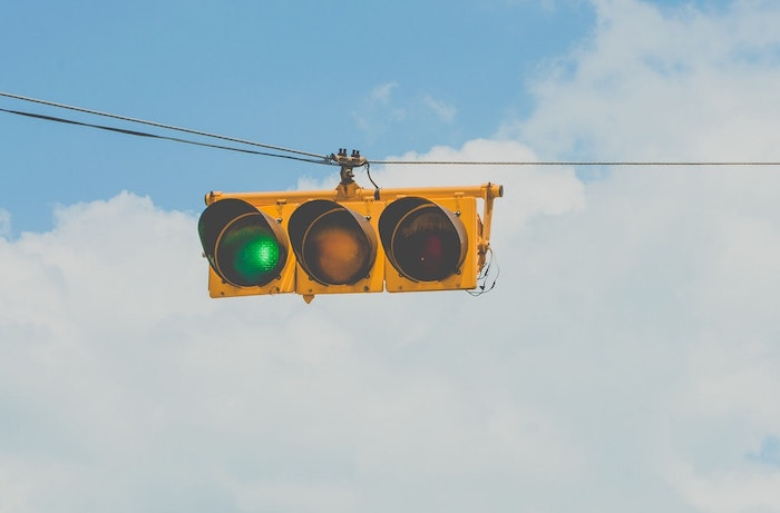 Green traffic light against blue sky with clouds