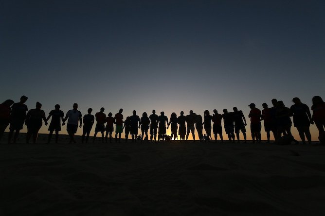 A silhouette of a group of people standing in a line on a hill