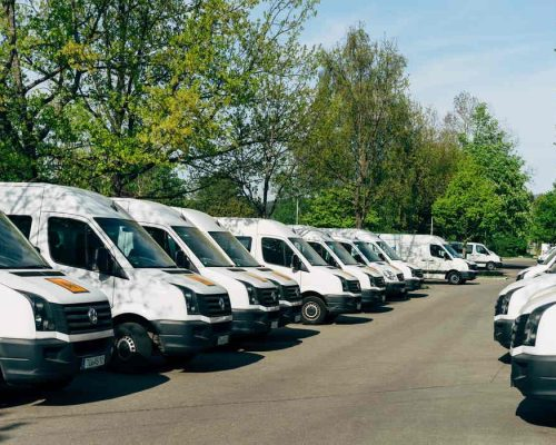 Multiple white vans parked in a row