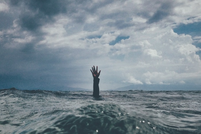 Hand emerging from rough sea