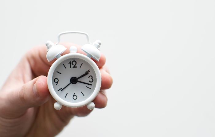 Hand holding tiny white alarm clock