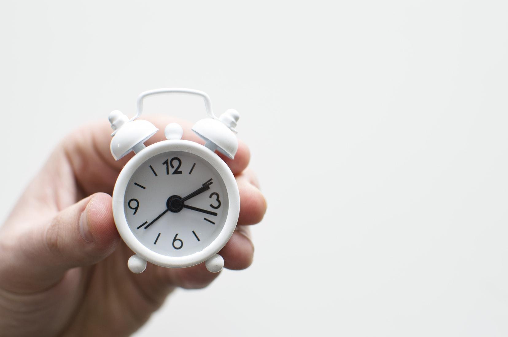 Hand holding mini alarm clock