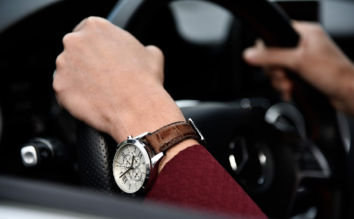 Hands with watch holding steering wheel