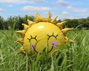 Balloon shaped like a sunshine with a happy face lying in the grass