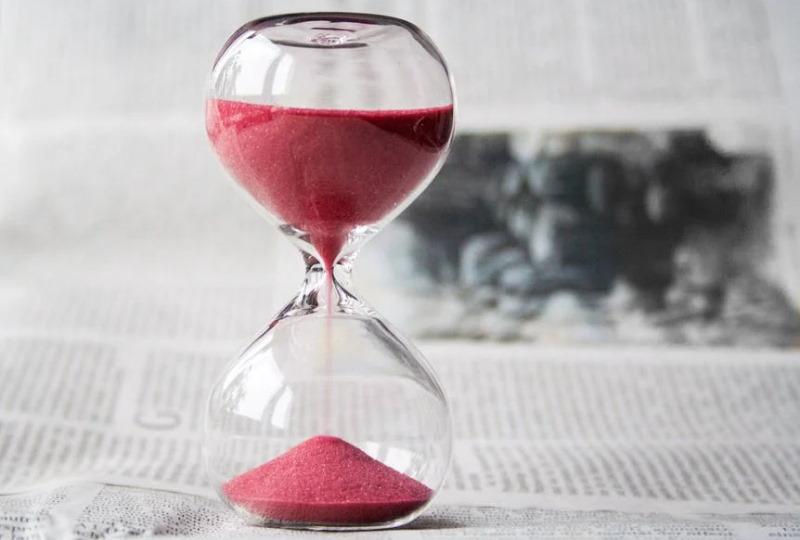 Pink sand running through hourglass standing on newsprint